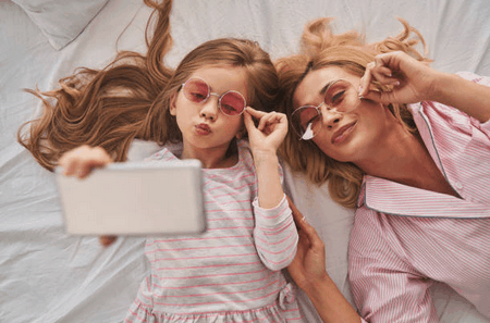 Happy family with phone on bed