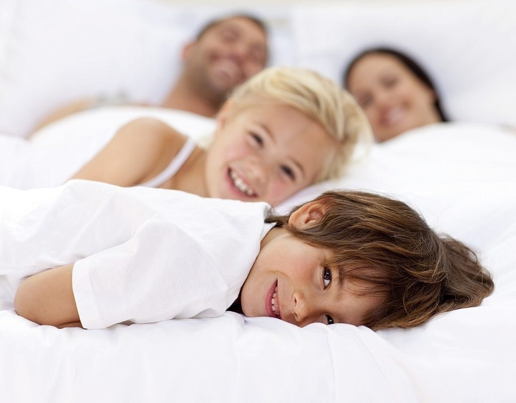 Happy family sleeping together on natural bed