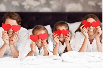 Happy family with hearts on eyes on a bed
